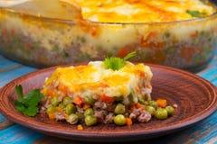 Cocotte en terre de pomme de terre, de fromage, de viande, de carotte, d'oignon et de pois Image libre de droits