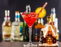 Coctail和美丽的圣诞节房子,蜡烛,瓶背景 免版税库存照片