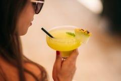 Coctail в руке женщины на пляже Желтое coctail с дыней стоковая фотография rf