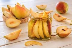Coctail av päron, päronskivor i sirap, nya päron och skivade päron på vita träbräden Arkivbilder