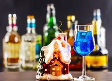 Coctail and beautiful Christmas house, candle, bottle background Stock Photos