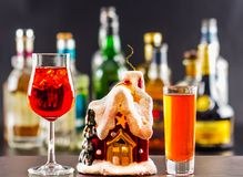 Coctail and beautiful Christmas house, candle, bottle background Stock Image