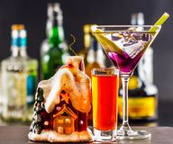 Coctail and beautiful Christmas house, candle, bottle background Stock Images