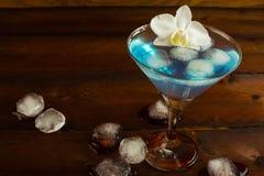 Coctail blåa Martini på den mörka träbakgrunden Arkivbild