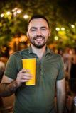 Coctail de consumición o cerveza del hombre hermoso en el partido de tarde de la noche del parque de la calle foto de archivo libre de regalías