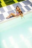 Coctail de jeune femme et amusement potables de avoir par la piscine Photographie stock