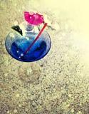 Coctail exponeringsglas med det lilla paraplyet, limefrukt på sand Arkivbild