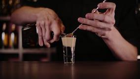 Coctail för bartenderdanandealkohol i restaurang Den sakkunniga bartendern tillfogar ingredienscoctailen på nattklubben lager videofilmer