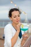Coctail för kvinnastands- och drinkblue fotografering för bildbyråer