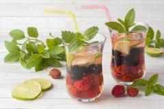 Coctail med den svarta vinbäret, jordgubben, mintkaramellen och limefrukt svalnande drinksommar arkivfoton
