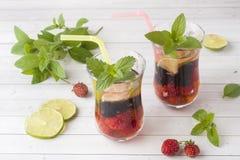 Coctail med den svarta vinbäret, jordgubben, mintkaramellen och limefrukt svalnande drinksommar arkivbilder