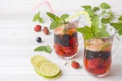 Coctail med den svarta vinbäret, jordgubben, mintkaramellen och limefrukt svalnande drinksommar royaltyfria bilder