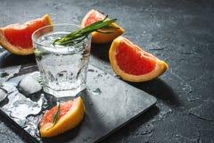 Coctail med grapefrukten, is och rosmarin på mörk stenbakgrund fotografering för bildbyråer