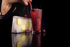 Coctail med jordgubben för ung flicka på svart, coctail för drink för kopieringsutrymmekvinna med iskuben Arkivbild