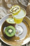 Coctail med kiwiskivan i ett exponeringsglas på en platta, bakgrund för brunt papper Grön drink, selektiv fokus Arkivfoto