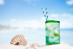 Coctail med is, rom, citronen och mintkaramellen i ett exponeringsglas på stranden Royaltyfri Fotografi