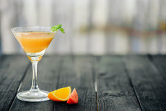 Coctail with orange and tomato on black wooden table at blurred background Stock Images