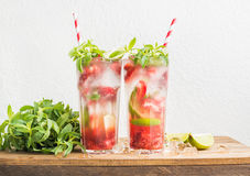 Coctailar för jordgubbemojitosommar med mintkaramellen och limefrukt i högväxta exponeringsglas arkivbild