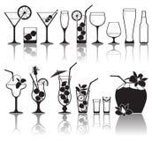 Coctailar och exponeringsglas med alkohol Arkivfoto
