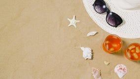 Coctailar, solhatt och solglasögon på strandsand lager videofilmer