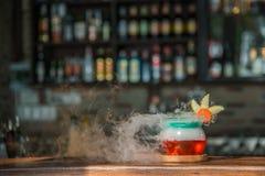 Coctaildrink i favör med rök på träplattan Arkivfoto