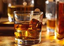 Coctailexponeringsglas av whiskey på trä bommar för Arkivfoto