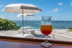 Coctailexponeringsglas framme av tabeller med paraplyer och en koralllagun Royaltyfri Foto