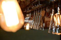Coctailexponeringsglas hänger från taket av stången Royaltyfri Foto
