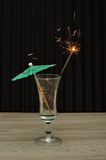 Coctailparaply med ett tomtebloss i ett coctailexponeringsglas Arkivfoto