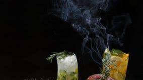 Coctails frescos de servicio con la antorcha culinaria Romero ardiendo con humo Cámara lenta Asación del romero para a almacen de metraje de vídeo