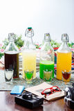 Coctails in glassy bottles and glass. On wooden table with accessories stock photography