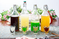 Coctails in glassy bottles and glass. On wooden table with accessories royalty free stock photos