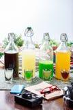 Coctails in glazig flessen en glas stock fotografie