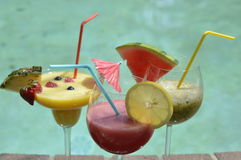 Coctails. Pineapple, kiwi and berries  coctails  by the pool Royalty Free Stock Photos