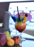 Coctails on a pool bar. A tequila sunrise and a curacao coctail served with a decoration of fresh fruits royalty free stock image