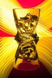 Coctailwhisky per exponeringsglas med styckis av partireflexionen ett begrepp av gula ljusa effekter för timglas på rött Fotografering för Bildbyråer