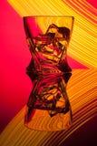 Coctailwhisky per exponeringsglas med styckis av partireflexionen ett begrepp av gula ljusa effekter för timglas på rött Arkivfoto