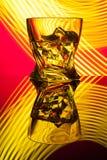 Coctailwhisky per exponeringsglas med styckis av partireflexionen ett begrepp av gula ljusa effekter för timglas på rött Royaltyfri Fotografi