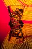 Coctailwhisky per exponeringsglas med styckis av partireflexionen ett begrepp av gula ljusa effekter för timglas på rött Arkivbilder