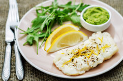 Cod baked with lemon and spices with arugula and mashed green pe. As on a dark background. tinting. selective focus stock images