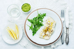 Cod baked with lemon and spices with arugula and mashed green pe Stock Image