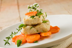 Cod on carrot bed with fresh oregano and basil Royalty Free Stock Image