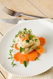 Cod on carrot bed with fresh oregano and basil Stock Photo