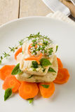 Cod on carrot bed with fresh oregano and basil Stock Photography