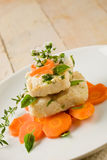 Cod on carrot bed with fresh oregano and basil Royalty Free Stock Photo