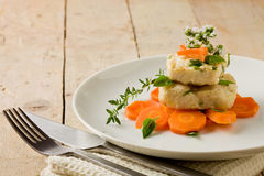 Cod on carrot bed with fresh oregano and basil Royalty Free Stock Photography