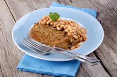 Cod fillet in bread crumbs with baked beans Stock Photography
