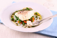 Cod fillet on fork with green beans, peas, parsley, olive oil. Close up Stock Photo