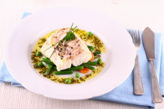 Cod fillet with green beans, peas, parsley, olive oil Stock Image