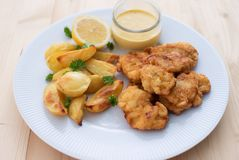 Cod fish in batter or cod fritters served with baked potatoes with parsley leaves and home made mayonnaise sauce. Stock Image